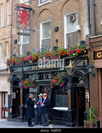 Fullers Red Lion pub with three drinkers, Piccadilly,London, England - Stock Image