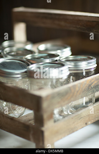Canning jars in wooden crate, close up - Stock Image