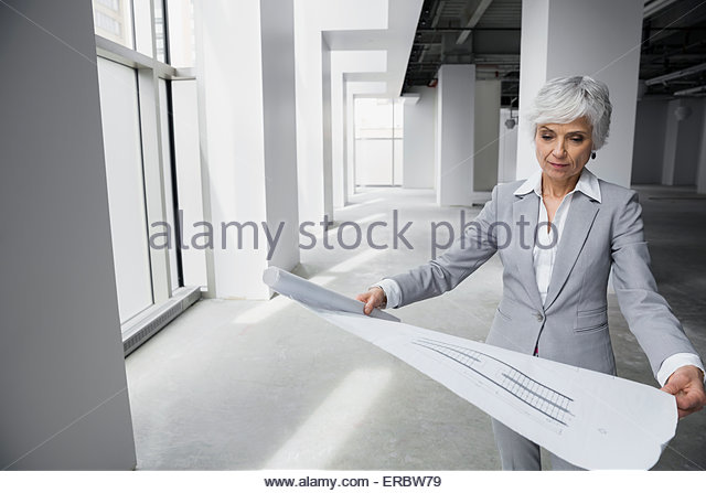 Architect reviewing blueprints in new office - Stock Image