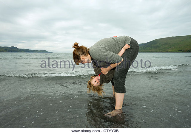 Mother and daughter playing in waves - Stock-Bilder