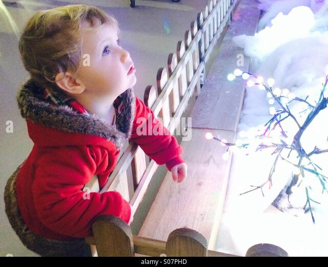 Little girl staring at Christmas lights in wonder - Stock Image
