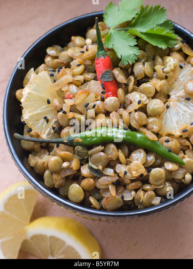 Bowl of Green Lentils cooked with Sliced Lemon Chili and Coriander - Stock Image