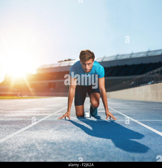 Fit and confident man in starting position ready for running. Male athlete about to start a sprint looking at camera - Stock Image