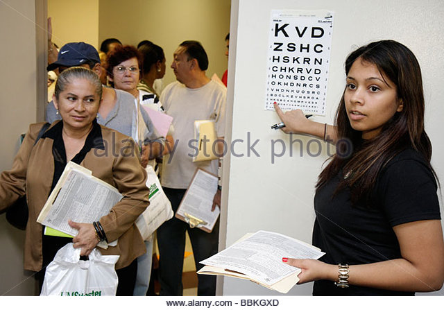 Miami Florida Liberty City Jessie Trice Community Health Center fair free care exam volunteer Hispanic woman ophthalmology - Stock Image