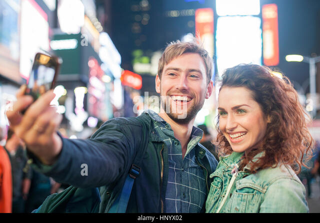Young couple taking selfie in Times Square, New York City, New York, USA - Stock Image