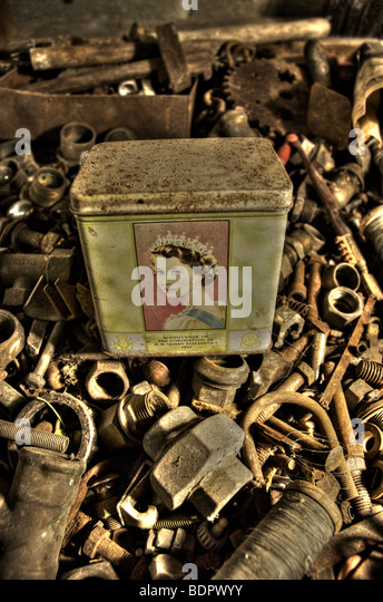 An old tin with a picture of Queen Elizabeth II in a box of old nuts and bolts - Stock-Bilder