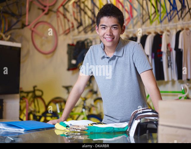 Portrait of young man looking at camera in bike shop - Stock Image