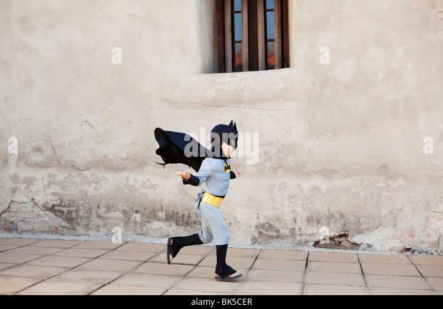 Boy in batman costume running - Stock Image