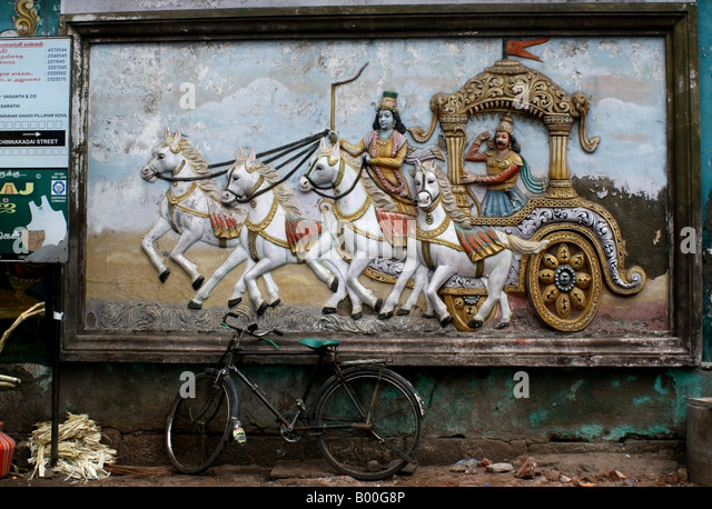 Bas relief of Arjuna riding the chariot to battle on a temple in Madurai , Tamil Nadu , South India - Stock Image