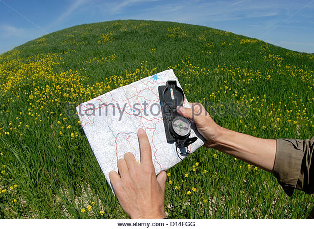 Man's hand holding compass map - Stock Image
