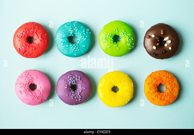 Colorful donuts on a blue background - Stock Image