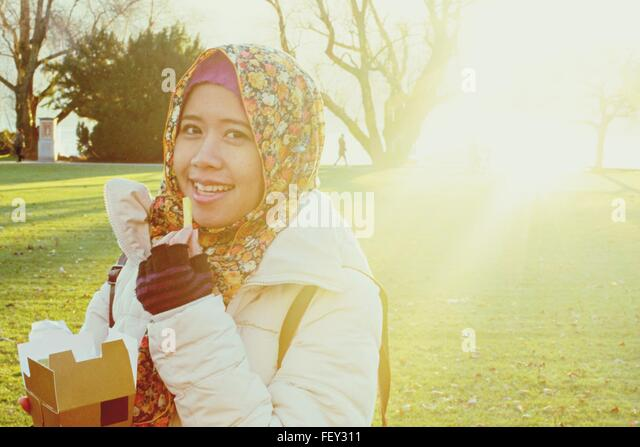 Smiling Woman Wearing Headscarf Eating French Fries While Standing At Park - Stock Image