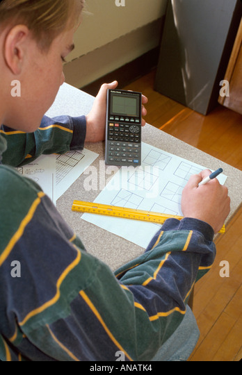New Jersey Haledon male teen student graphing calculator math class test - Stock Image
