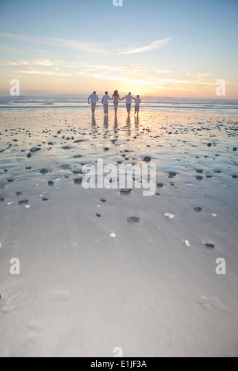Family running towards sea at sunset, Cape Town, South Africa - Stock Image
