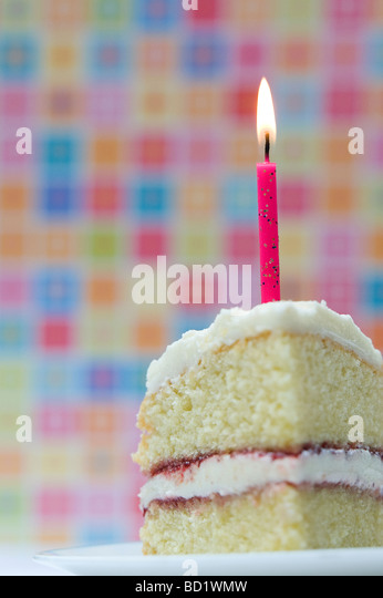 Slice of birthday cake with a lighted candle against a colourful pastel background - Stock Image