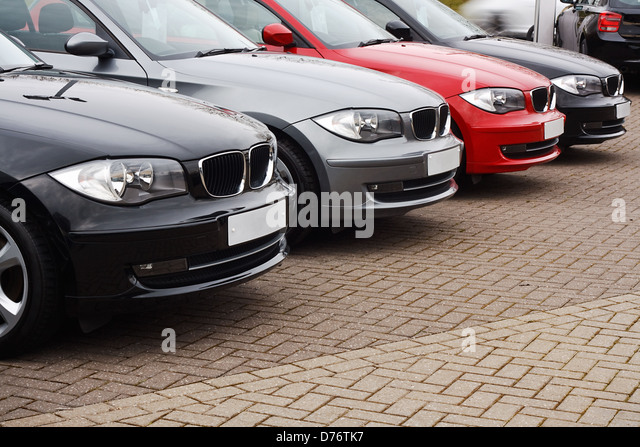 row of prestige used cars for retail sale in a motor dealers yard showing same model in different colour choices - Stock Image