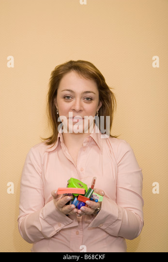 Portrait of a mid adult woman holding stationery objects - Stock Image