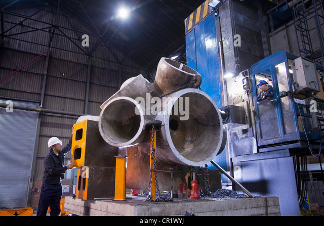 Worker using machinery in steel forge - Stock Image