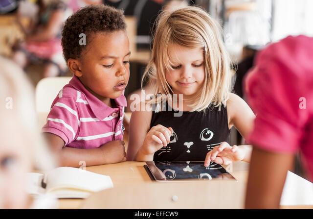 Children using digital tablet in classroom - Stock Image