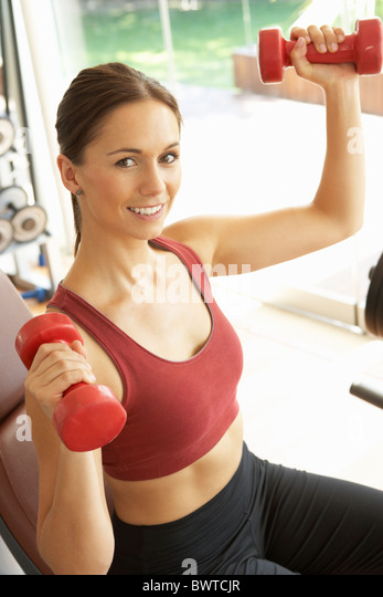 Young Woman Working With Weights In Gym - Stock Image