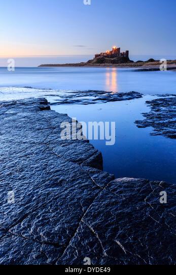 Looking towards Bamburgh Castle at dawn. - Stock Image