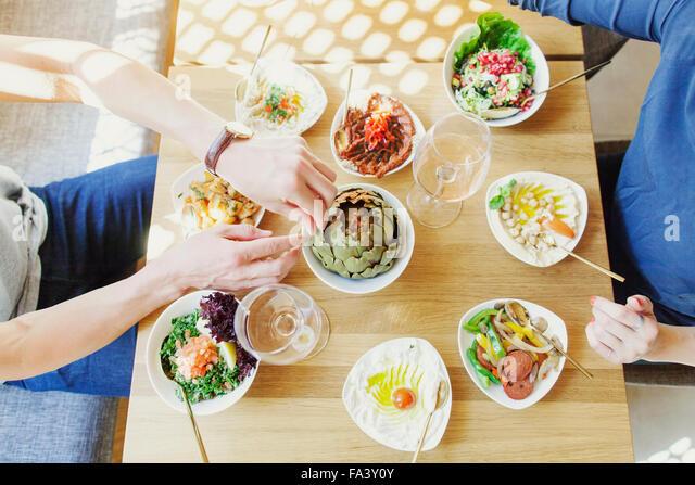 High angle view of couple having food in Lebanese restaurant - Stock-Bilder
