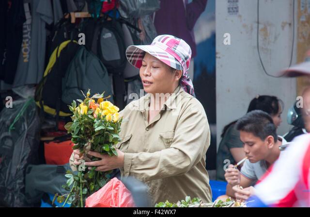 vietnamese street flower seller handing bunch of flowers to a purchaser,Hanoi,Vietnam - Stock Image