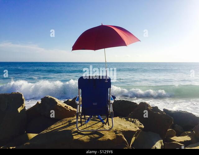 A single red umbrella and a blue chair at the beach. Ventura, California USA. - Stock Image