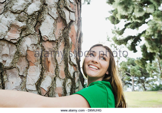 Happy young woman looking away while hugging tree in park - Stock Image