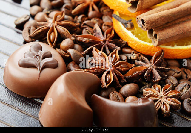 Fragrant spices, coffee and chocolate sweets on a dark striped background - Stock Image