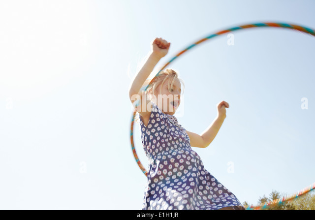 Low angle view of girl playing with plastic hoop - Stock Image