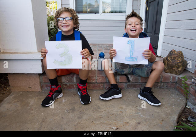Portrait of two brothers sitting in porch holding up pieces of paper with 3 & 1 - Stock Image