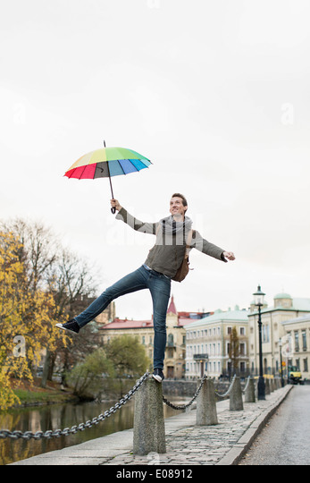 Full length of businessman with umbrella balancing on bollard outdoors - Stock Image