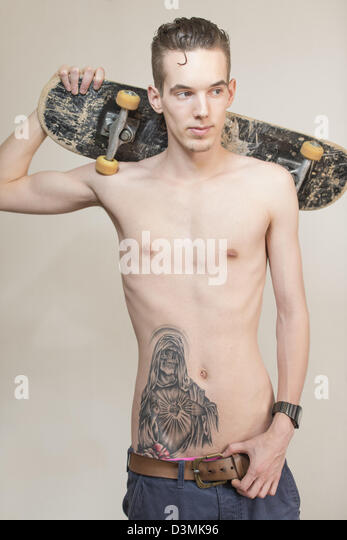 Confident and cool young adult man with tattoo holding a skateboard - Stock-Bilder