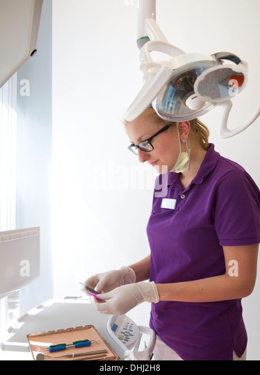 Dental trainee preparing equipment - Stock Image