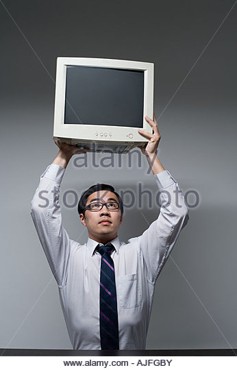 A businessman lifting a computer monitor - Stock Image