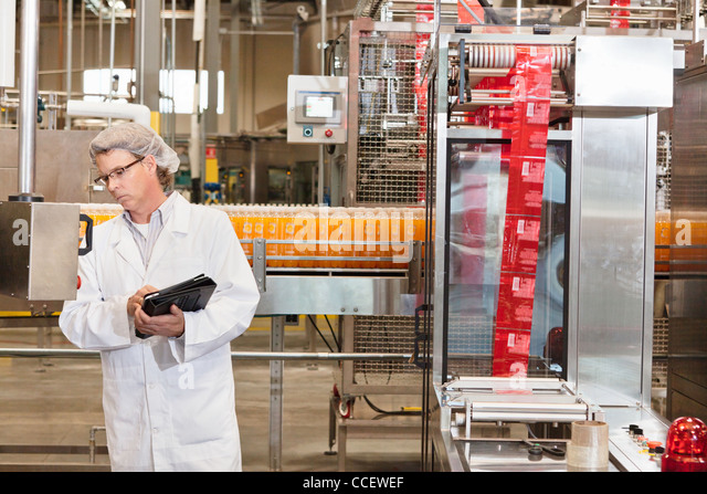 Middle-aged man having inspection at bottling industry - Stock Image