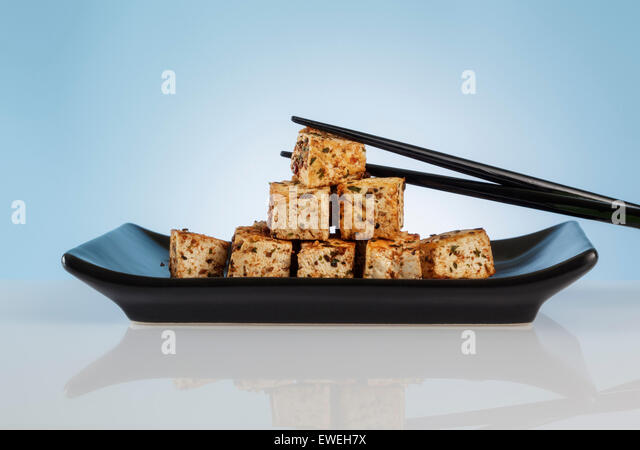 Spiced Tofu Cubes on black Dish - Stock Image
