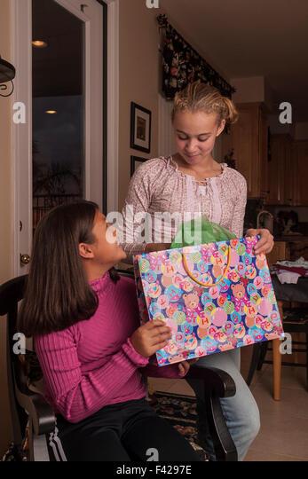 Korean and Brazilian best girl friends giving gift. MR ©Myrleen Pearson - Stock-Bilder