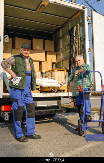 Two male movers unload furniture and boxes from moving truck - Stock Image