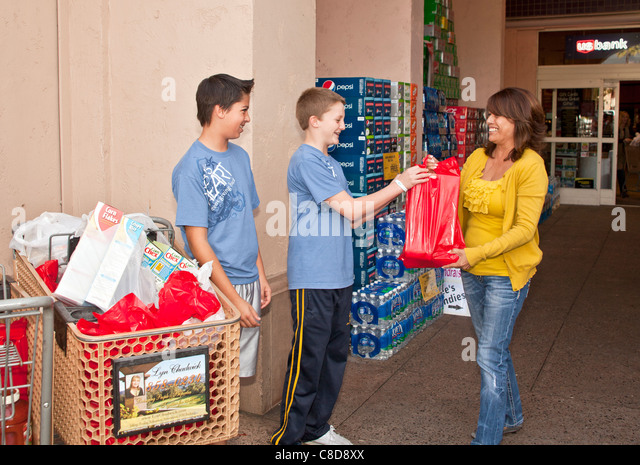 Teen boys from Lion's Heart organization collecting donations for food bank. MR © Myrleen Pearson - Stock Image