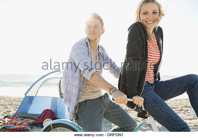 Couple cycling on beach - Stock Image