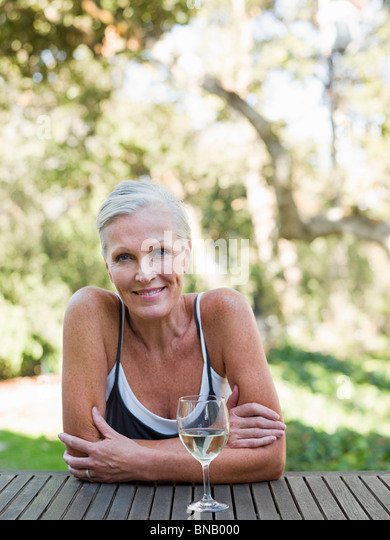 Mature woman outdoors with wine - Stock Image