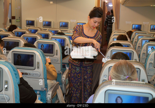 San Francisco California International Airport SFO onboard Singapore Airlines cabin Asian woman attendant employee - Stock Image