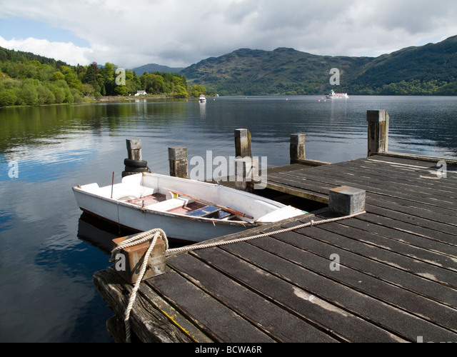 Rowing boat by a pier on Loch Lomond, Tarbet Scotland - Stock Image