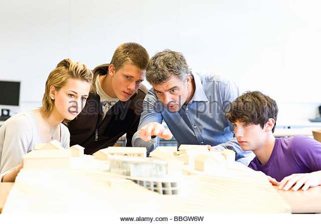Mature man and teens gathered around an architectural model - Stock Image
