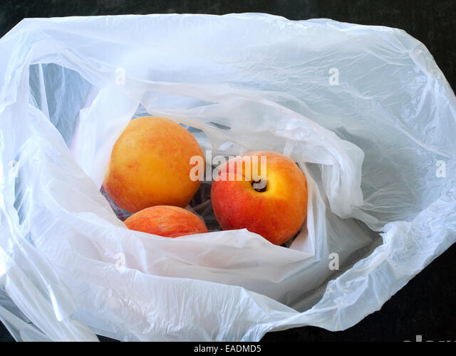 Peaches in bag on counter - Stock Image