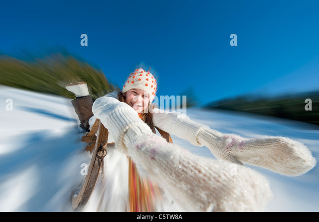 Austria, Salzburger Land, Altenmarkt, Girl (10-11) sledding, portrait - Stock Image