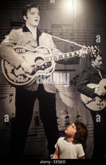 Boy looking up at photo of Elvis - Stock-Bilder