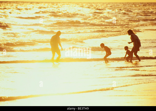 Young family enjoying beach at sunset - Stock Image